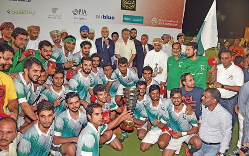 The victorious Pakistan Development Squad members celebrate with the trophy at the Sultan Qaboos Sports Complex on Friday