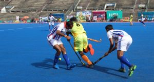 SNGPL player goes past 2 WAPDA players